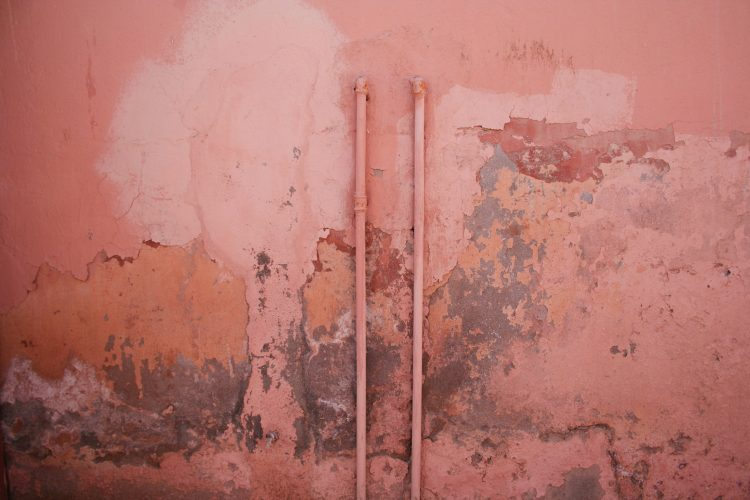 pink old wall with pipes nd black mold