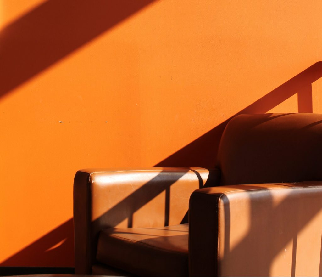 Faux Leather sofa chair with orange background shaded