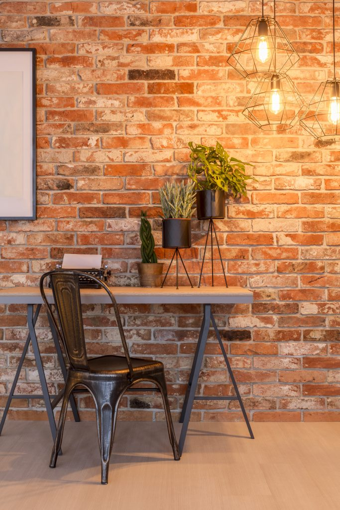 Simple home office with industrial with brick wall, chair, des