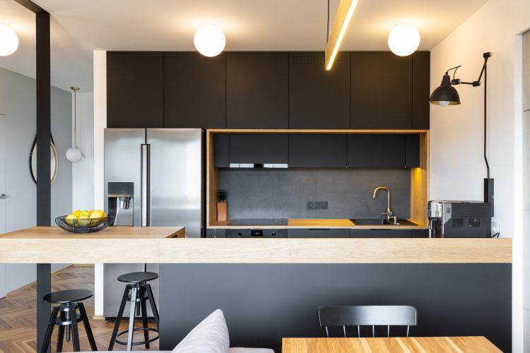 Black wooden furniture and an industrial lamp above a coffee machine in a beautiful, modern kitchen interior with dining space