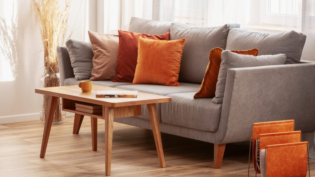 Living room with wooden coffee table and grey couch with ginger, orange and red pillows