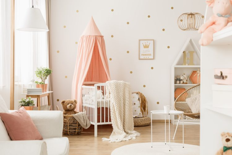 Bright nursery room interior with white crib, decoration, poster and gold dots on the wall