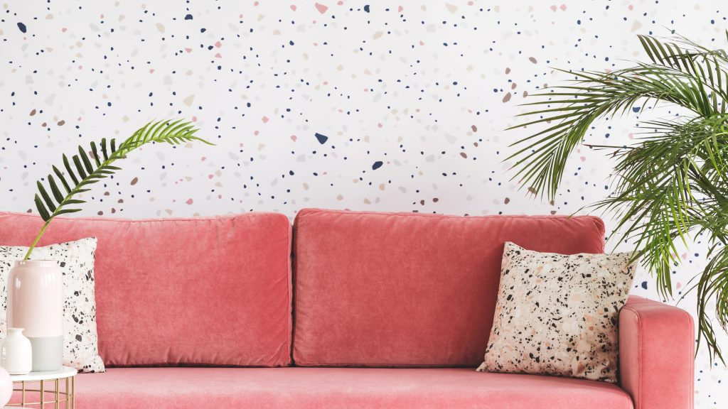 Real photo of a pink sofa with pillows, chandelier and patterned wall in the background in living room interior