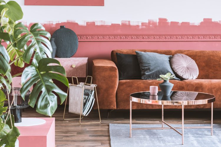 Trendy living room with ombre wall and brown velvet corner sofa with pillows