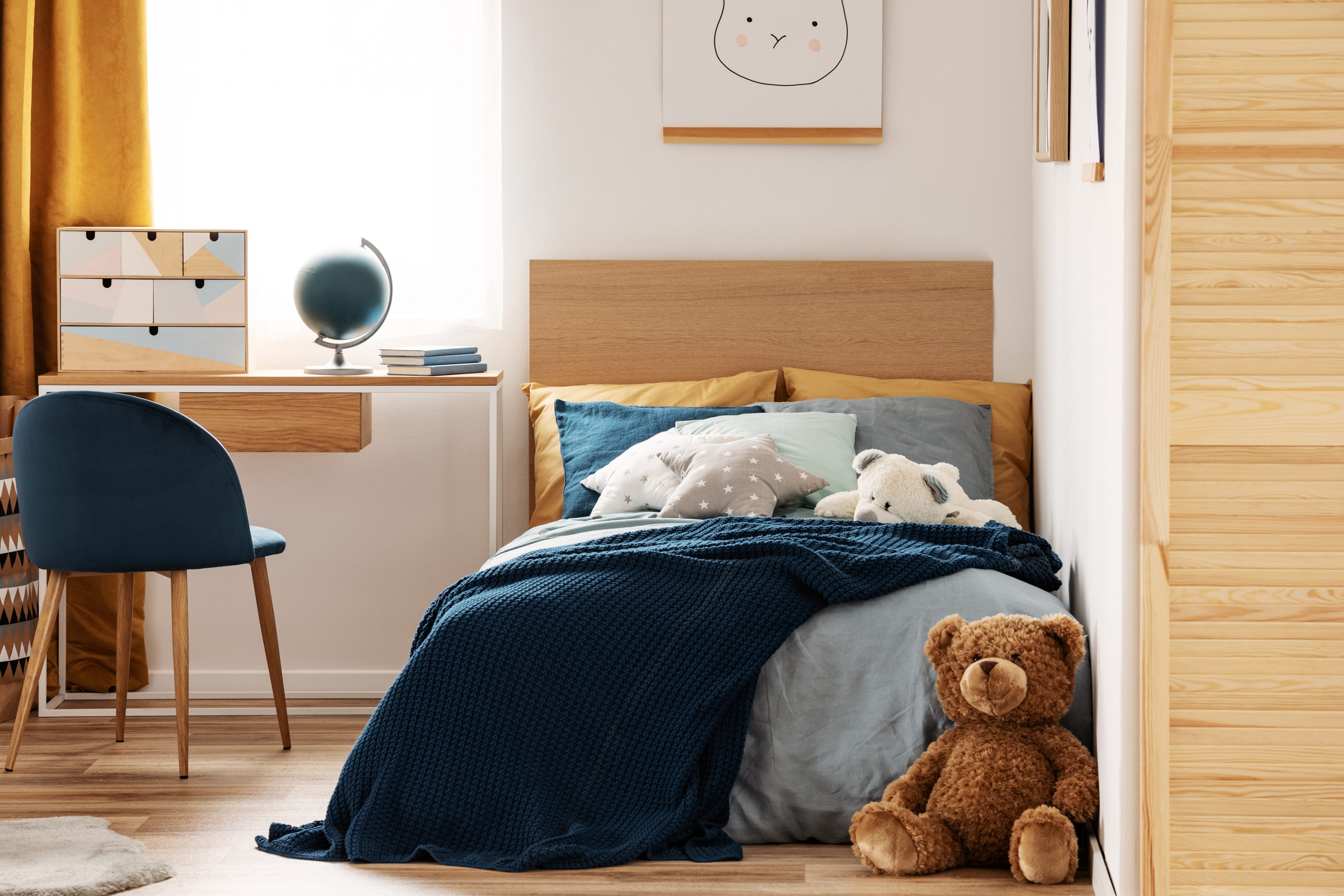 Brown cute teddy bear on wooden floor of stylish bedroom interior for kids