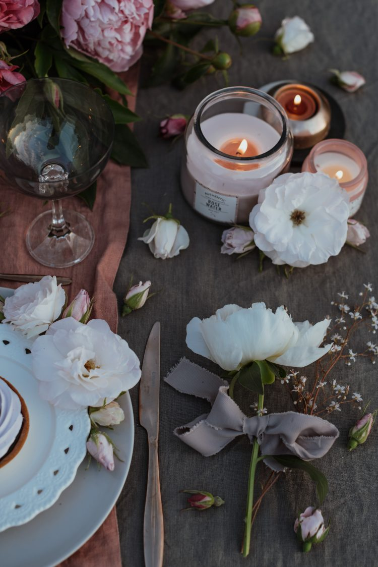 light pink flowers and candles on grey wooden table