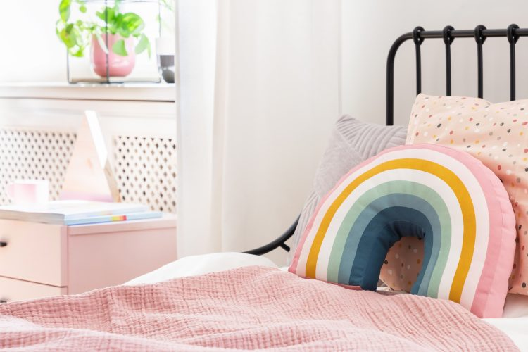 Pastel pillows on pink bed in girl's rainbow bedroom interior with white cabinet. Real photo