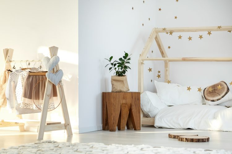 Stylish girl's room with bed and wooden accessories